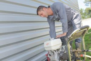 Man Starting Engine Of Portable Pressure Washer