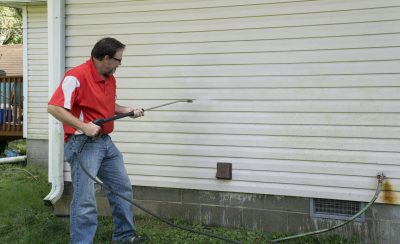 The ultimate guide on how to pressure wash your house Contractor Using A Pressure Washer To Clean Vinyl Siding