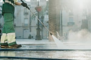Worker Cleaning The City Streets With High Pressure Gasoline Washer Splashing Dirt, Professional Cleaning Services. High Pressure Cleaning, Lower Body Best hot water pressure washer (Reviews and Buyers guide)