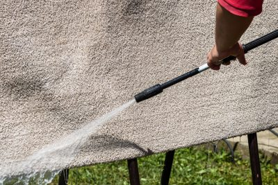 Can You Pressure Wash a Rug? Cleaning The Carpet With A Gun For Washing High Pressure Water. House Cleaning. Close Up Of Washing Carpets With High Pressure Washer. Cleaning The Carpet With A Gun For Washing High Pressure Water. House Cleaning Concept.